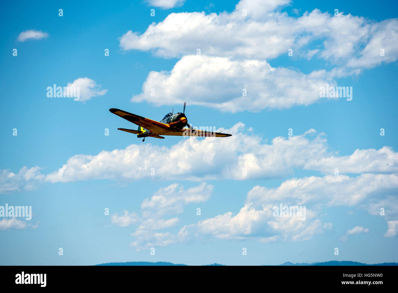 NAKAJIMA KI-43 OSCAR flying, front and bottom view, blue sky and white puffy clouds Stock Photo