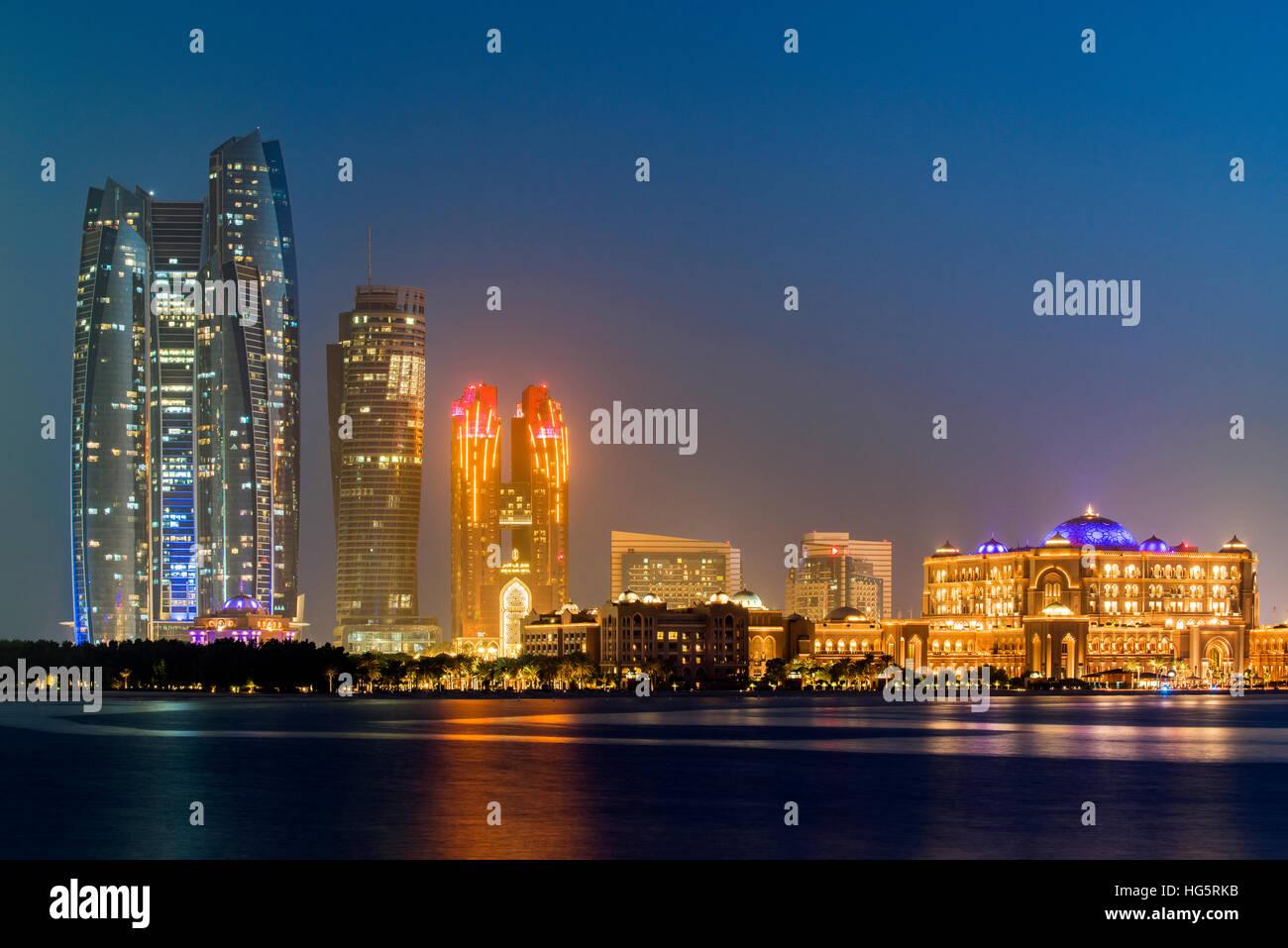 CIty skyline at twilight with Etihad Towers and Emirates Palace Hotel, Abu Dhabi, United Arab Emirates - Stock Image