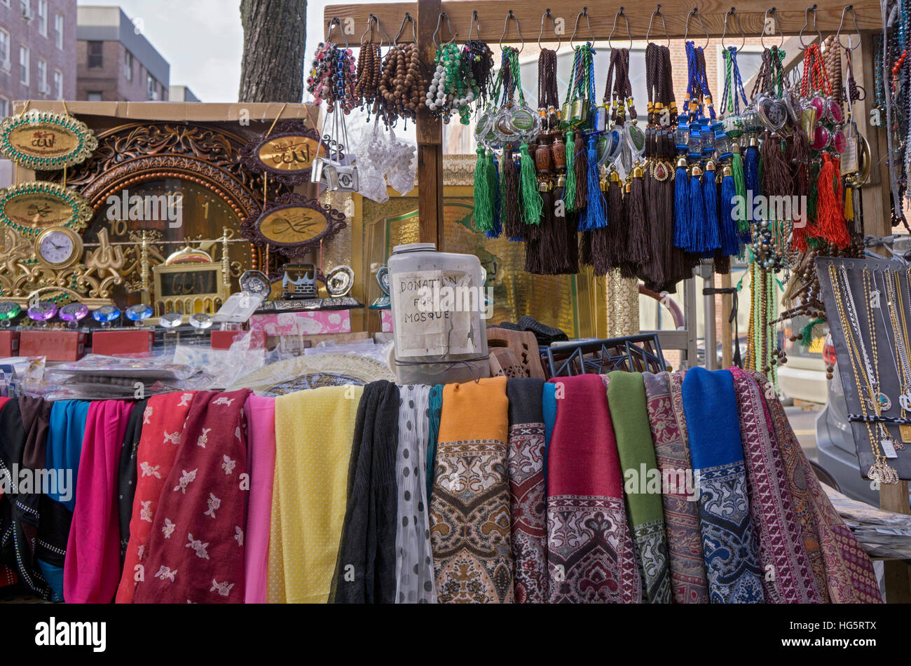 A Muslim merchants stand on 3th Ave., Jackson Heights NYC selling religious articles & with a charity box for - Stock Image