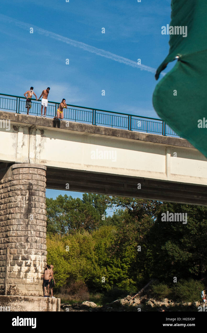 A group of young teenagers is jumping off a bridge into a river - Stock Image