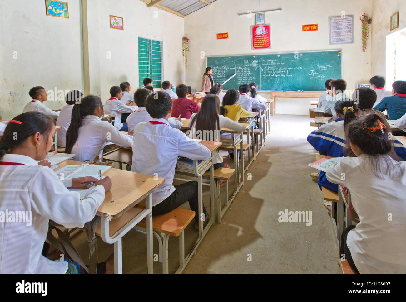 Students attending class, teacher instructing English lesson. Stock Photo