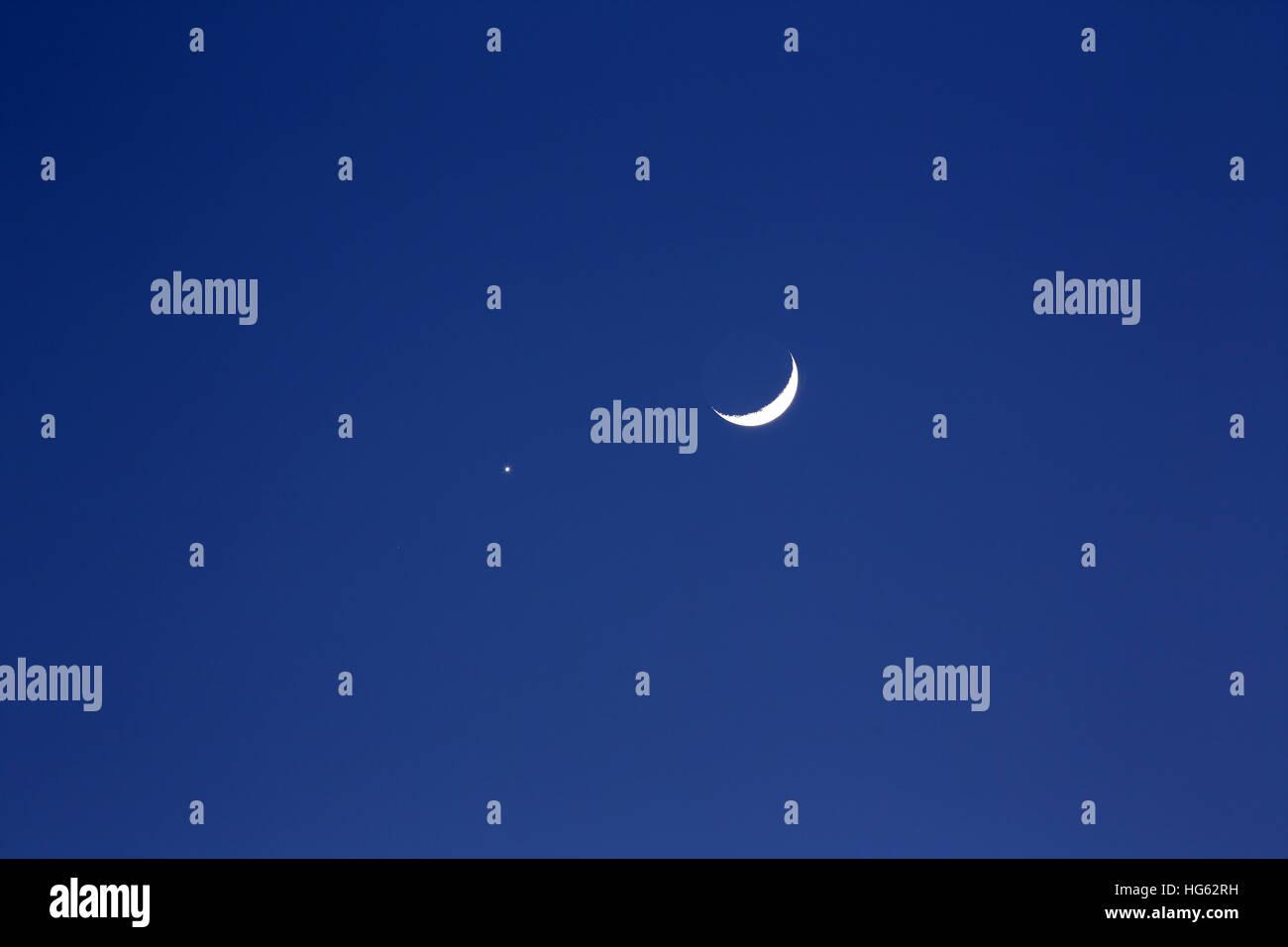 Crescent moon and planet venus, dark blue background - Stock Image