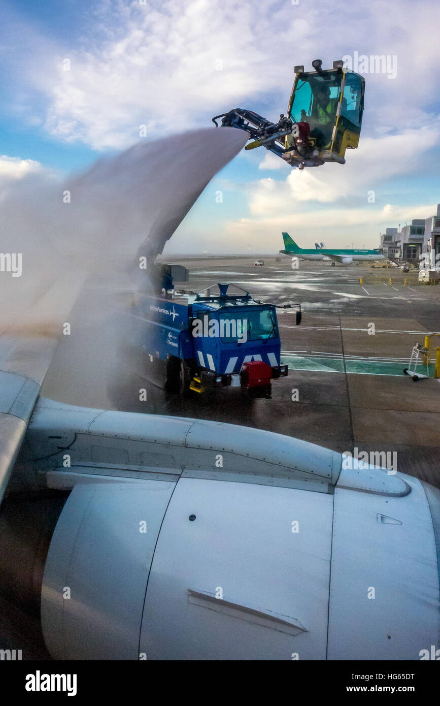 De-icing the wings of an airplane before departure from Gatwick Airport during the winter months - Stock Image