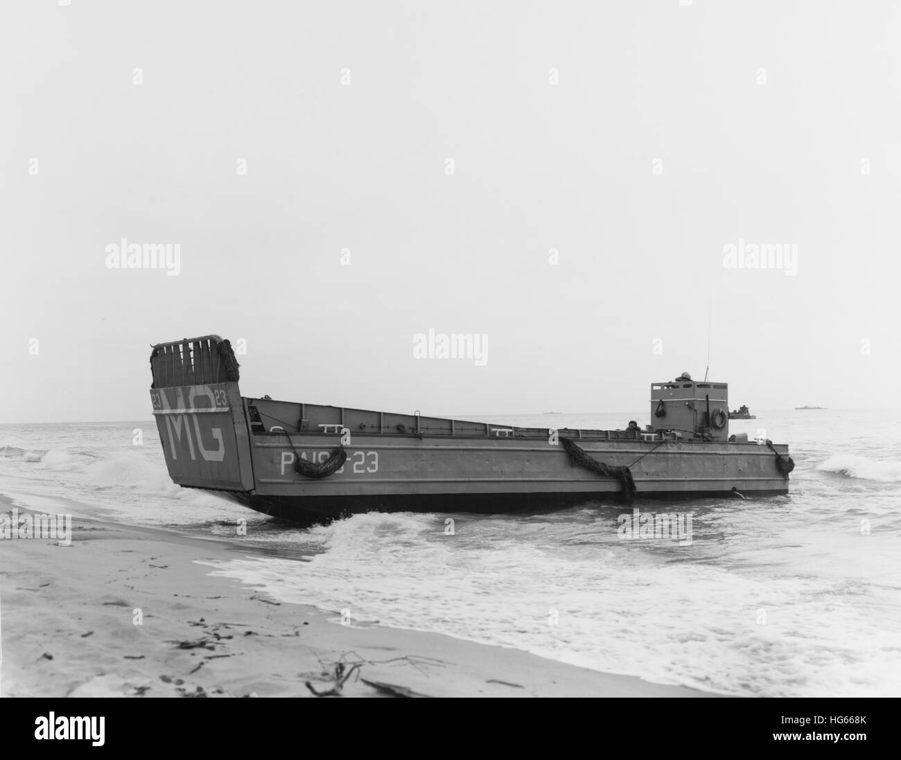 A landing craft beaches to unload troops during Operation Pony Express, 1961. - Stock Image
