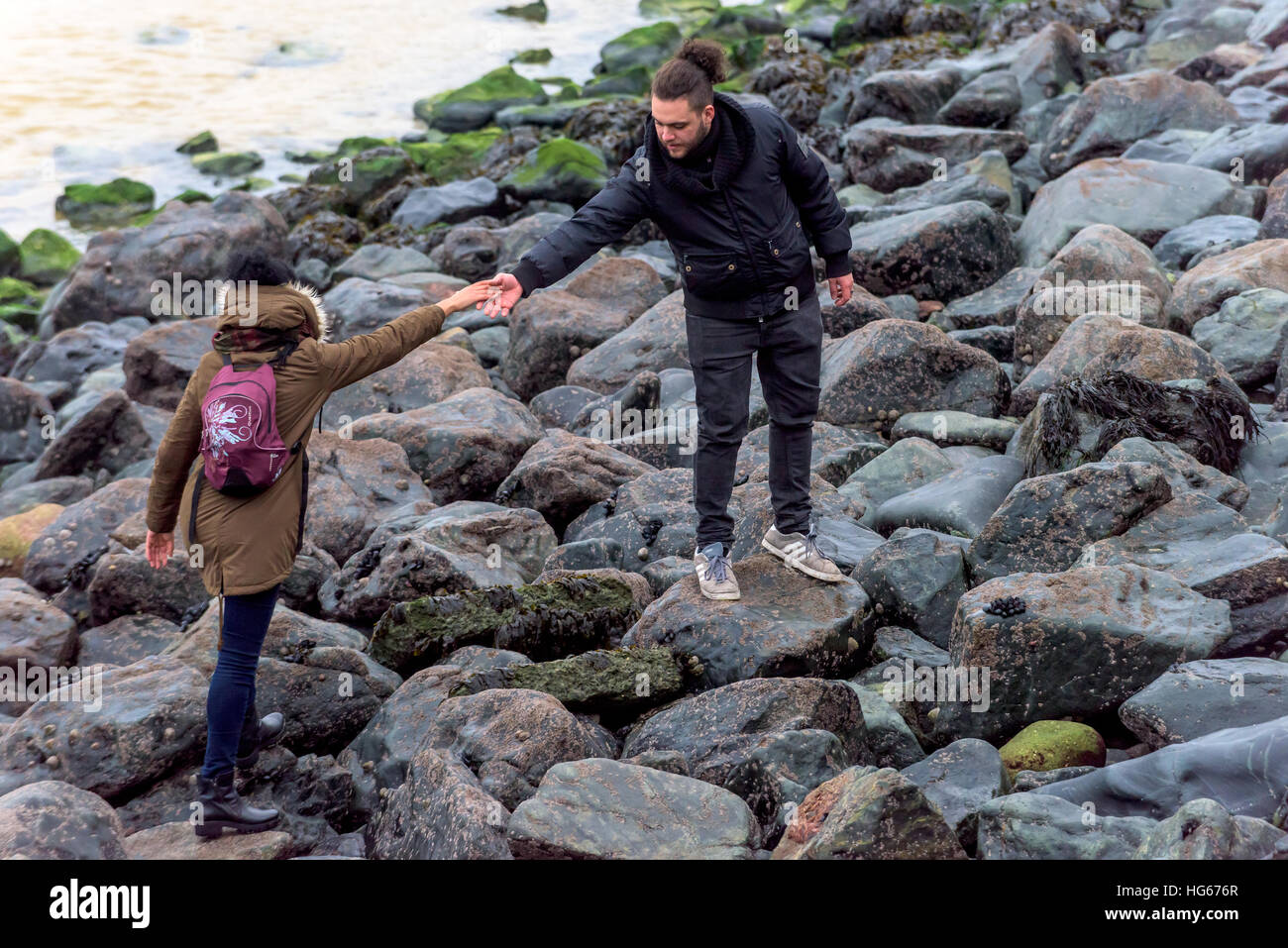 A young couple scramble over the rocks on the beach at St Ives in Cornwall - Stock Image