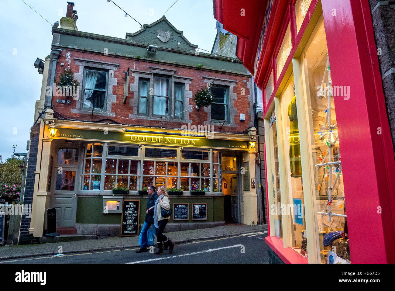 A couple walk past a pub in the colourful streets of St Ives in Cornwall - Stock Image