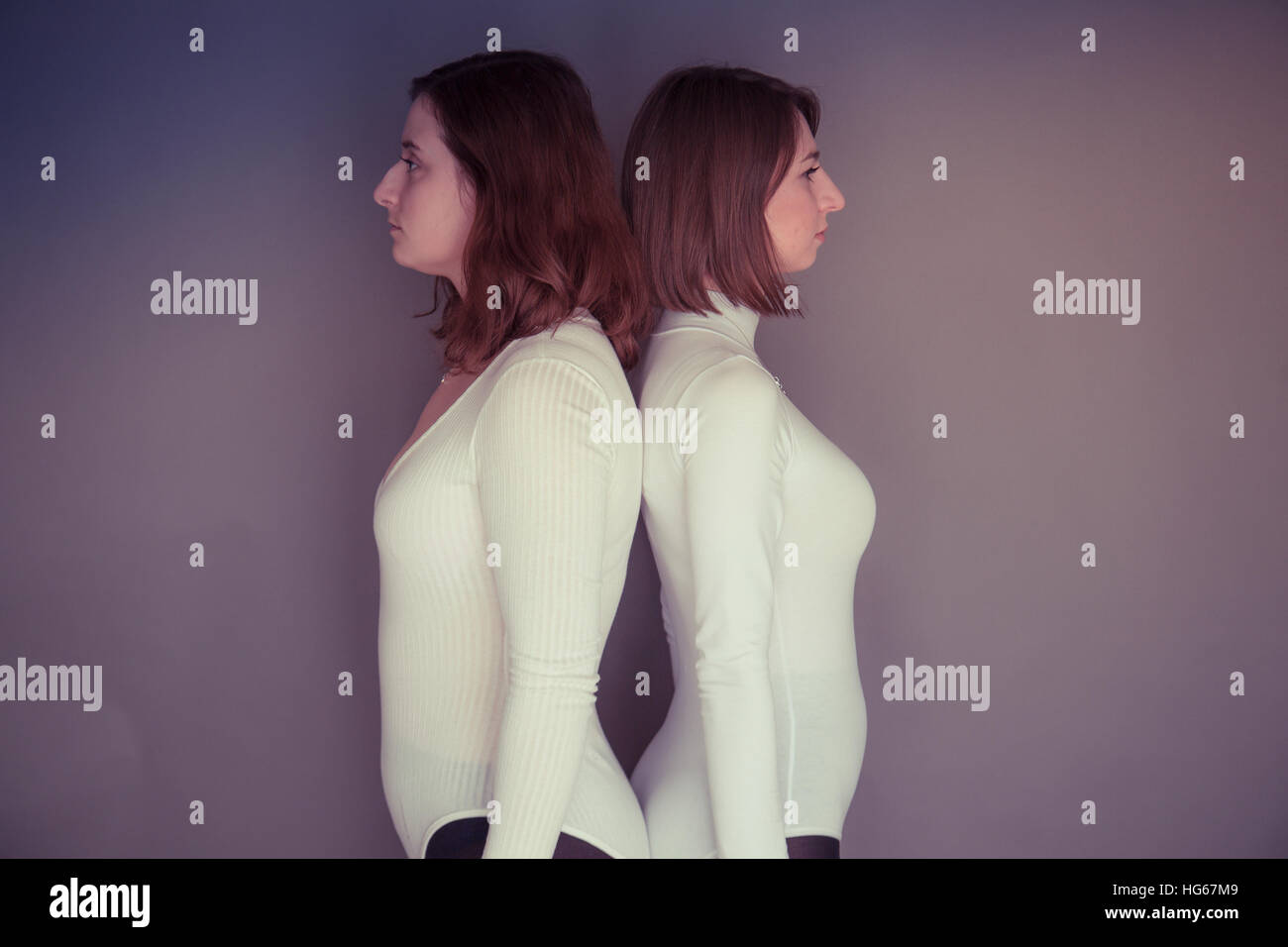 Doppelganger / Alter-ego themed photoshoot: two young women girls wearing matching clothes stood standing together - Stock Image