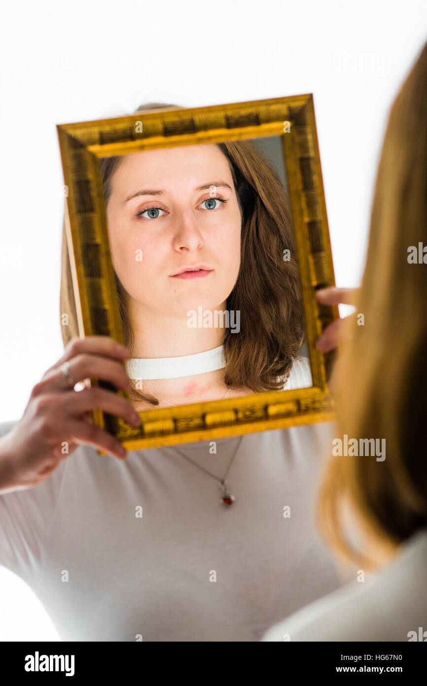 Doppelganger / Alter-ego themed photoshoot: a  young woman girl looking at her reflection in a mirror held my a - Stock Image
