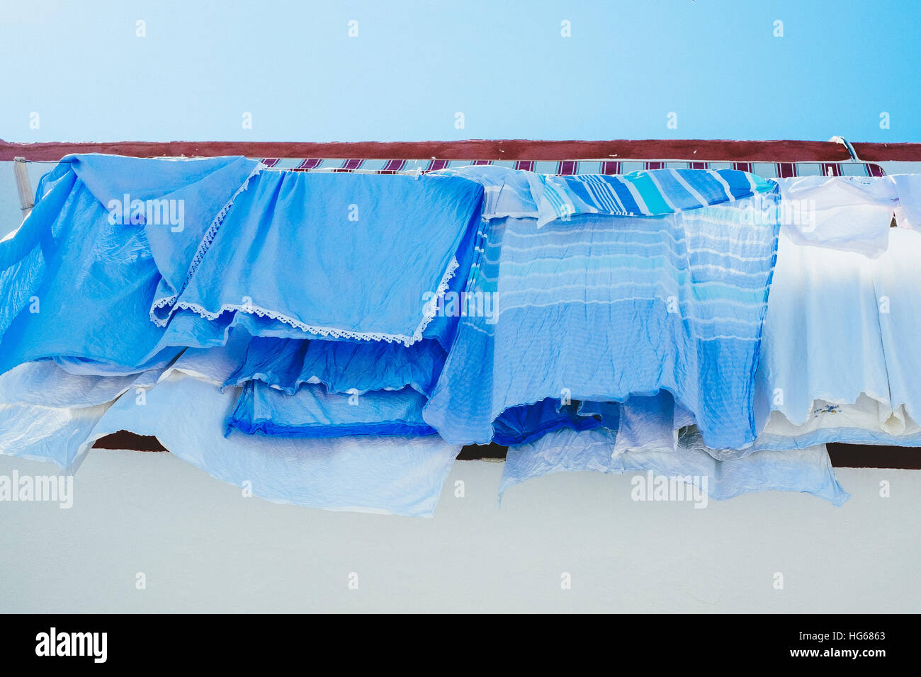 Colour-coordinated blue laundry drying on a clothesline on a sunny day on the island of Ischia, Italy, in the Bay - Stock Image