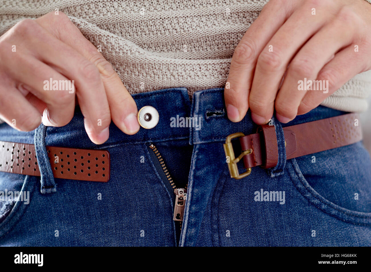 closeup of a young caucasian man trying to fasten his trousers, after his weight gain - Stock Image