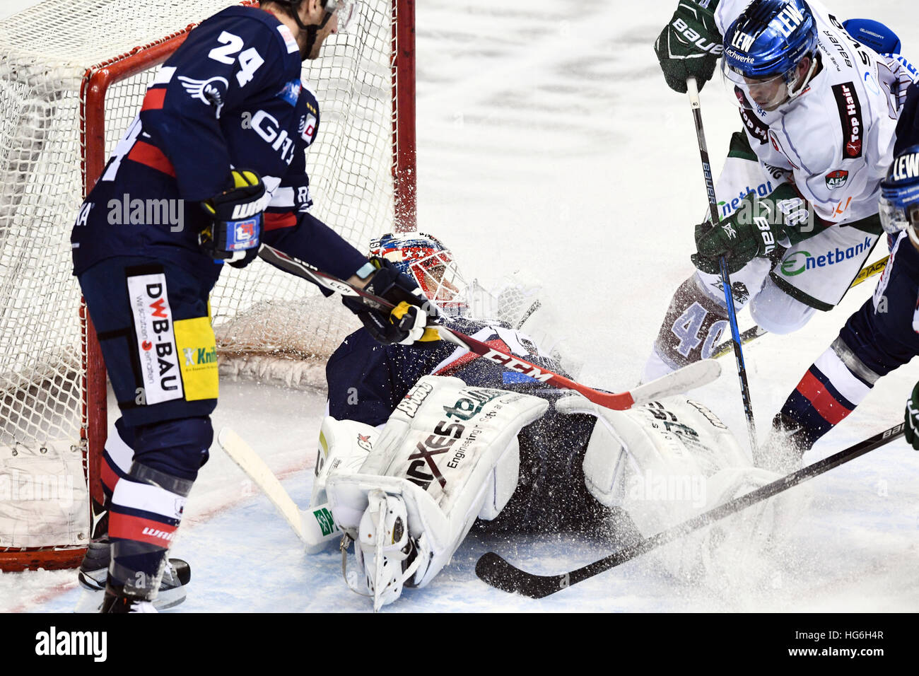 Berlin's Andre Rankel (L) and goalkeeper Petri Vehanen and Augsburg's Even Trupp vie for the puck during - Stock Image