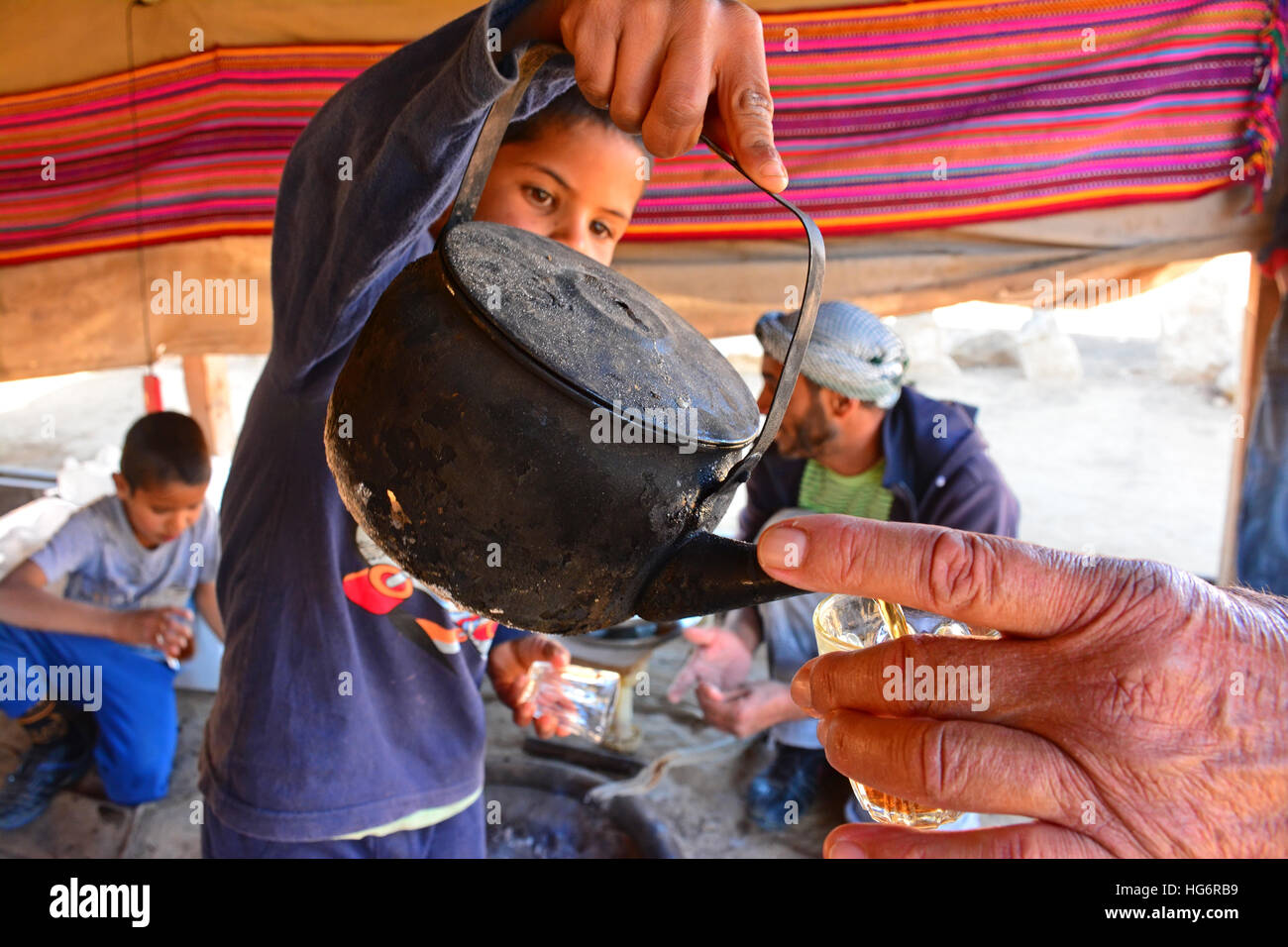 Bedouin kid serves tea to his father, Israel - Stock Image