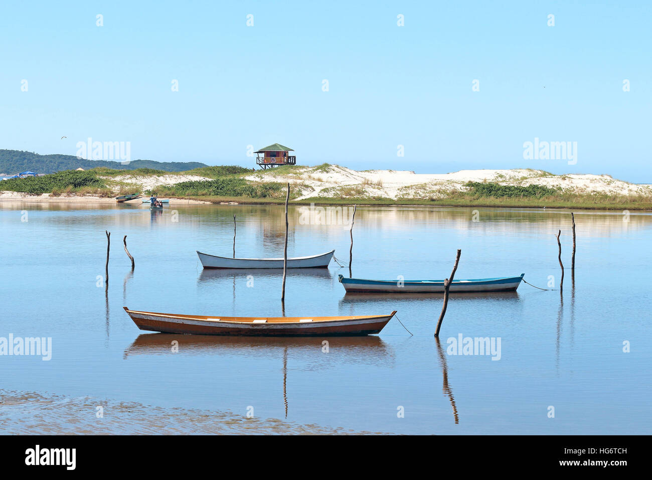 Boats moored on the beach, their reflection shines in the water. Beyond, the guardhouse and the sea! - Stock Image