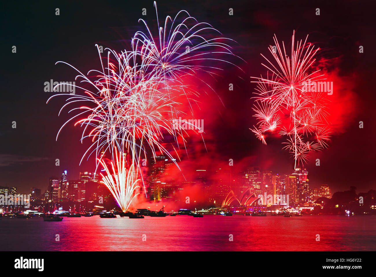 Bright red balls of new year eve fireworks in Sydney across illuminated waters of Harbour over skyscrapers of city - Stock Image