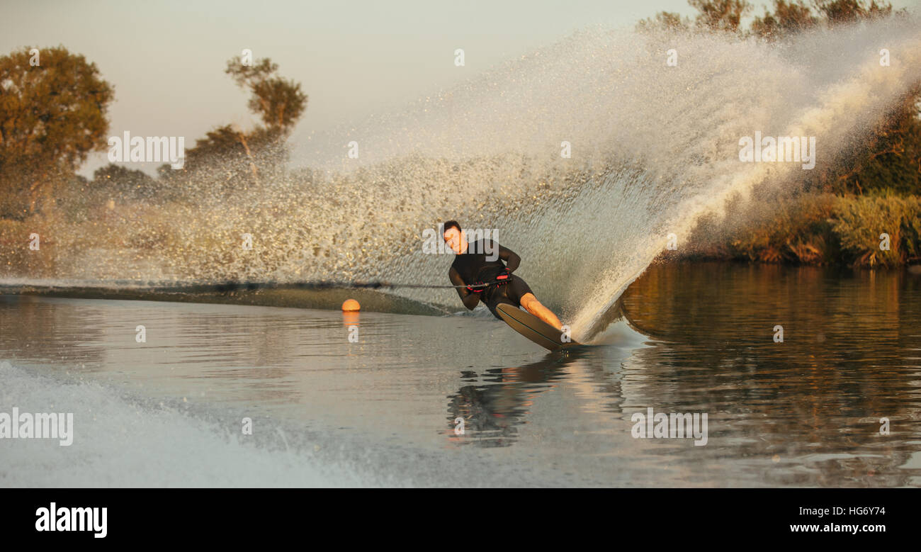 Man wakeboarding on a lake. Wakeboarder surfing across the lake. - Stock Image
