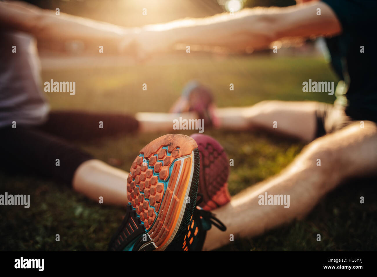 Feet of young man and woman exercising together in the park. Focus on shoes of couple working out together. - Stock Image