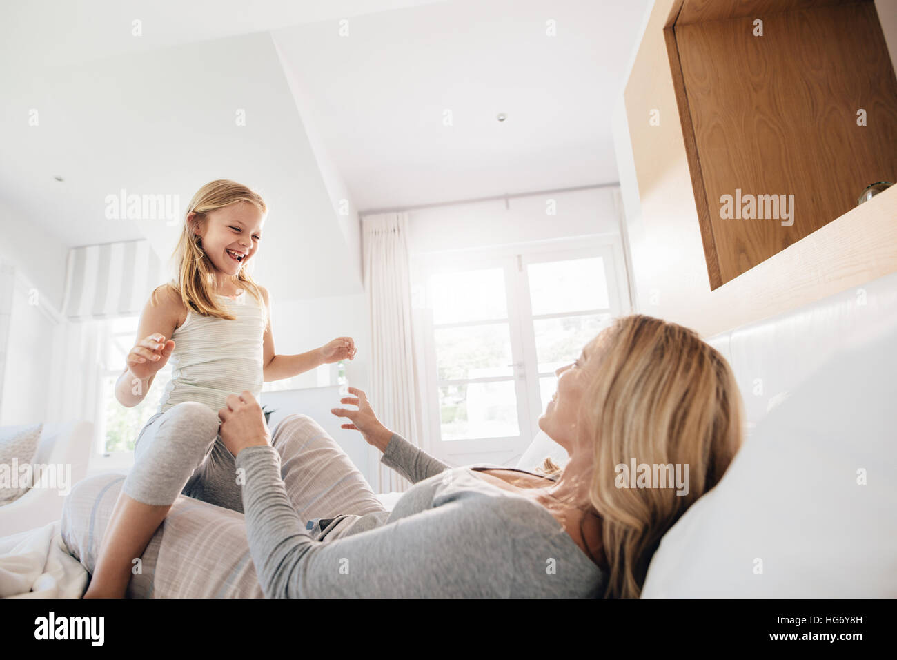 Indoor shot of little girl playing with her mother on bed. Mother and daughter playing in bedroom. - Stock Image