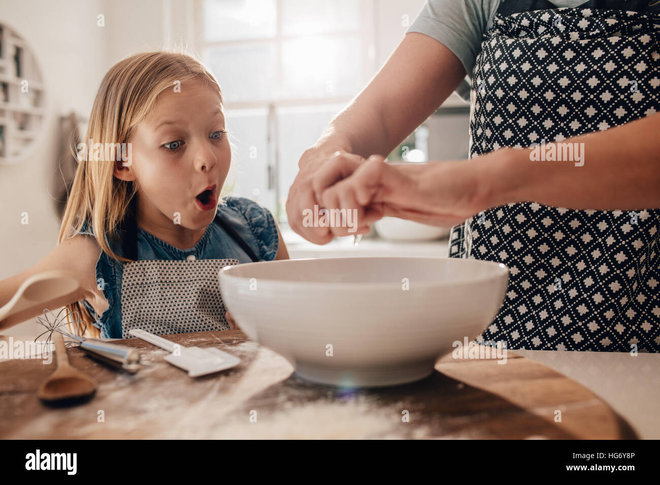Excited young girl with mother preparing dough for baking. Woman hands cooking with daughter standing by in kitchen. - Stock Image