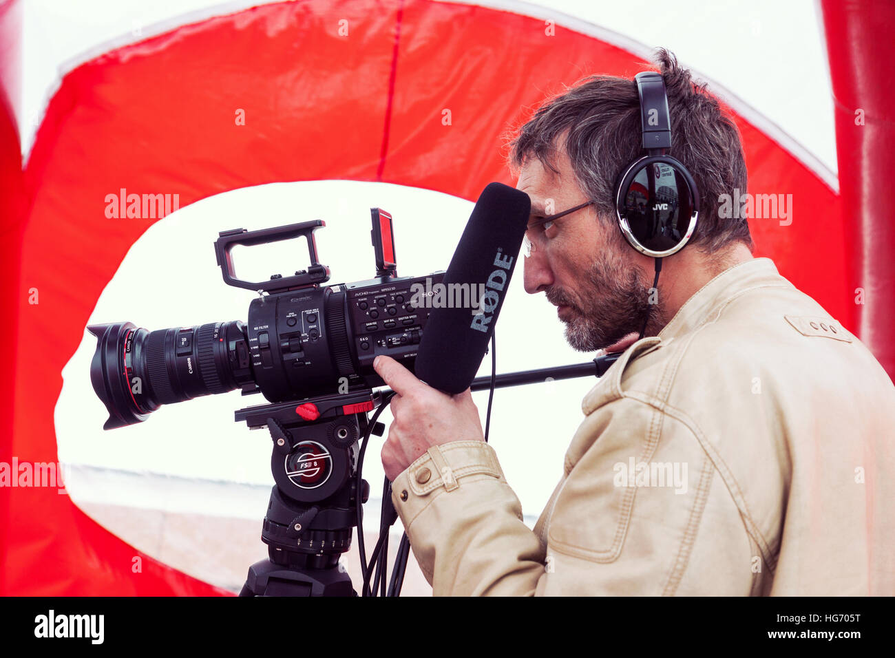 Closeup of cameraman shooting event on the street in Vilnius, Lithuania - Stock Image