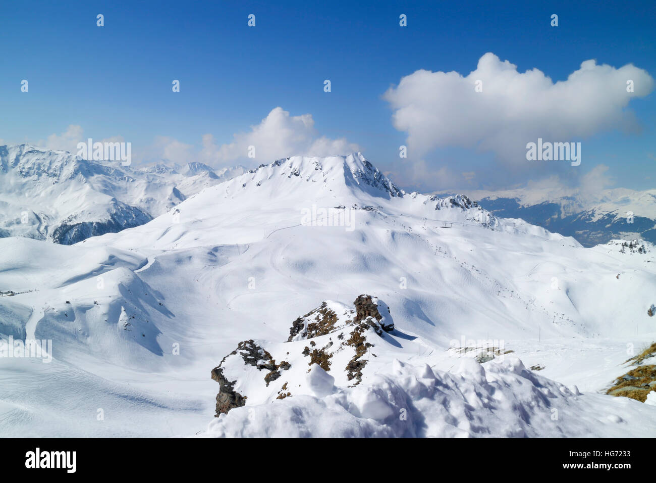 Winter Alps panorama with downhill ski slopes, high up lifts on cloudy day, Paradiski, Plagne resort, France - Stock Image