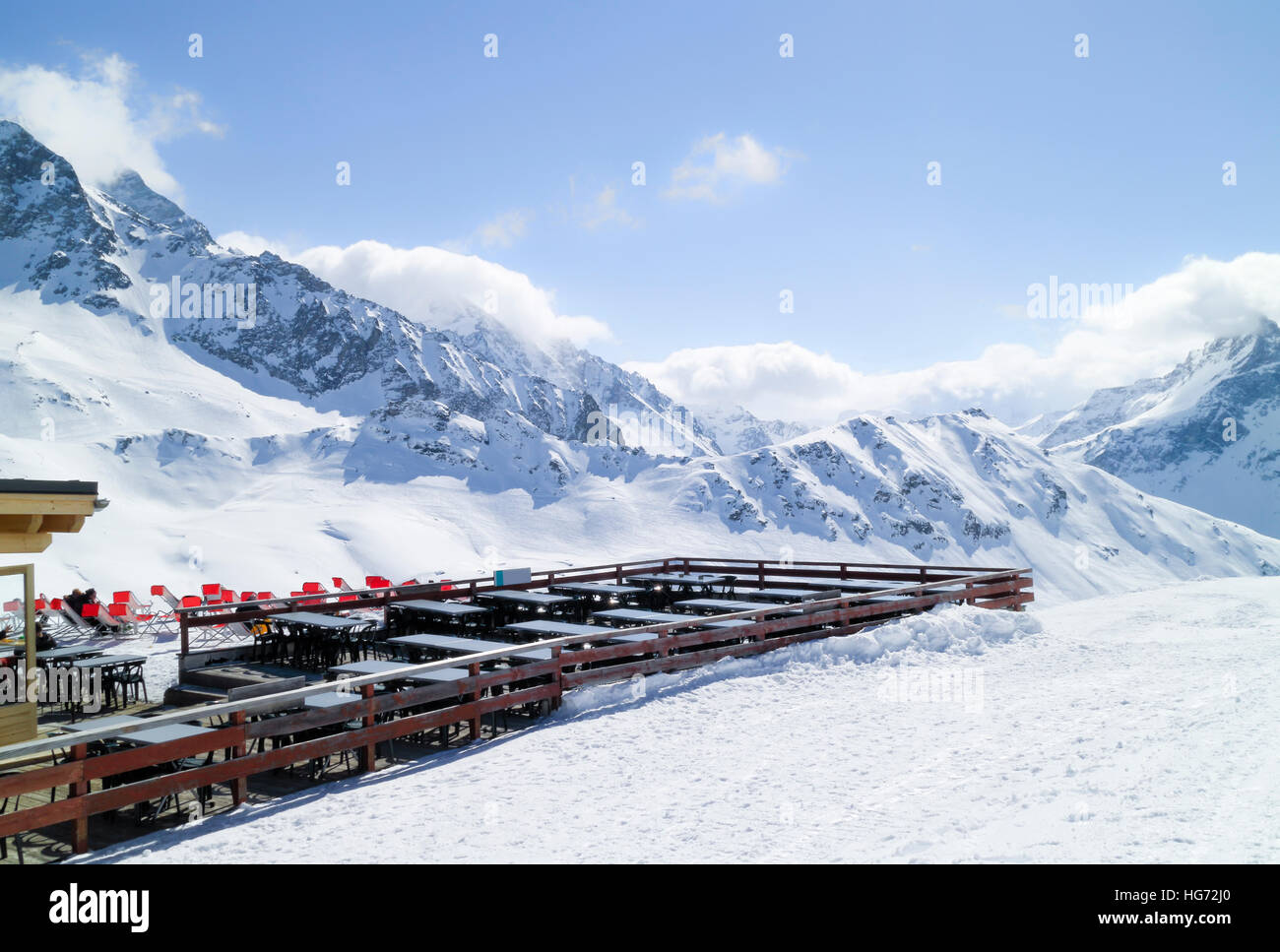 Apres ski chalet restaurant with chairs and tables outside, facing snowy mountain peaks and slopes, Les Arcs, Alps, - Stock Image
