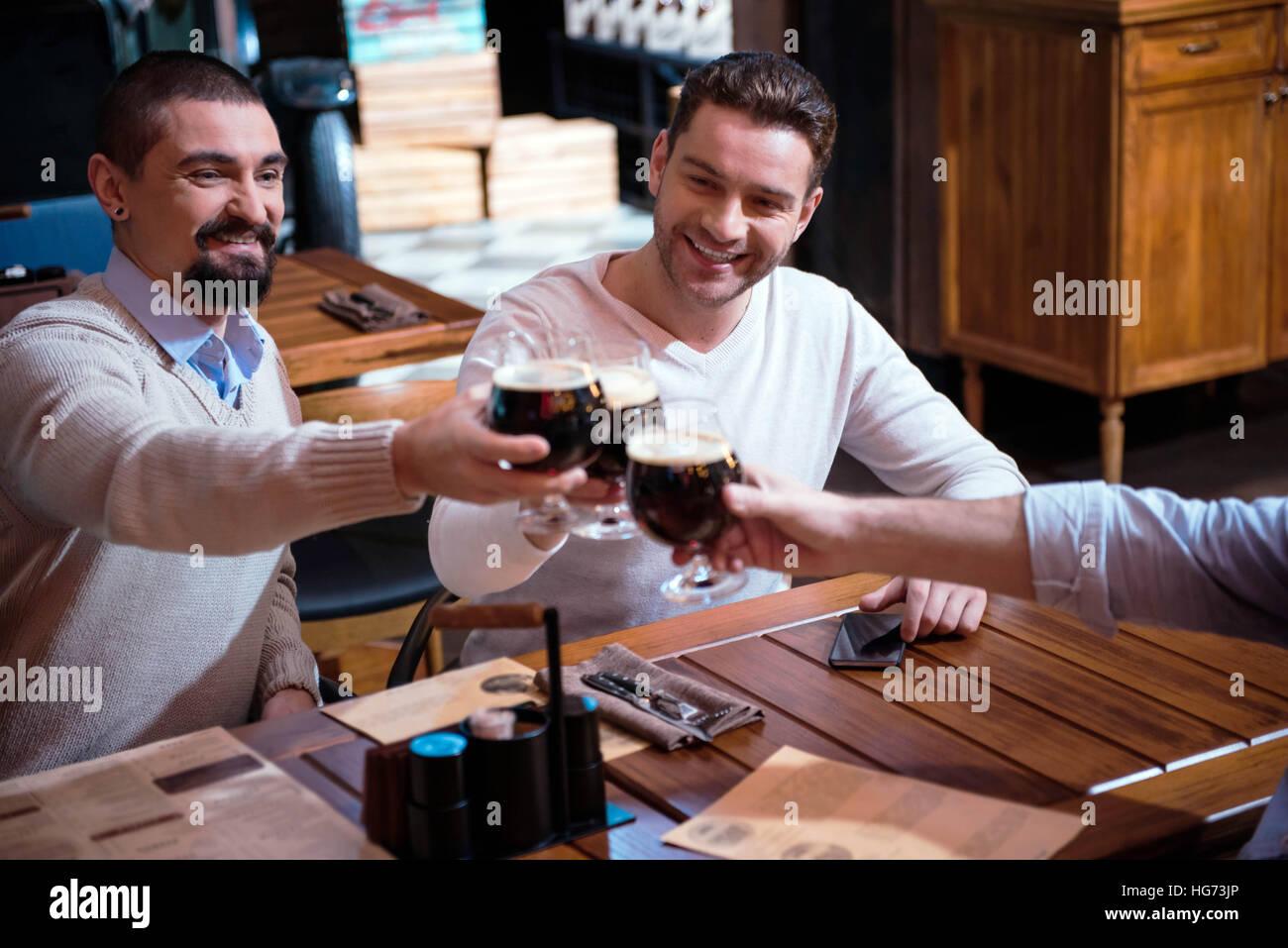Positive joyful friends cheering with beer - Stock Image