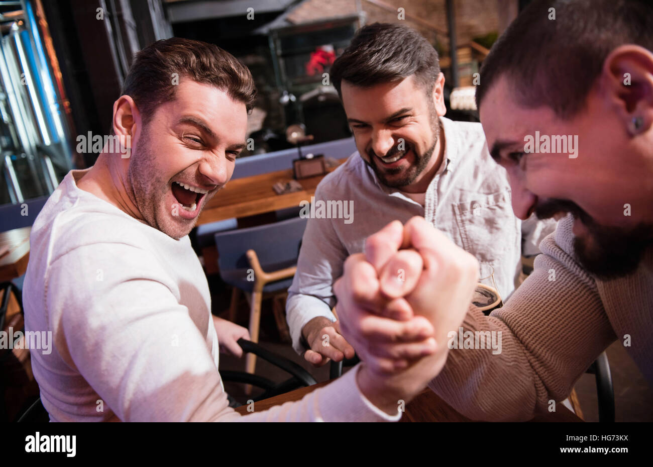 Nice handsome man trying to win the armwrestling match - Stock Image