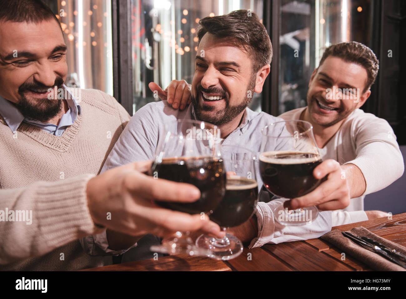Joyful delighted men drinking alcohol - Stock Image