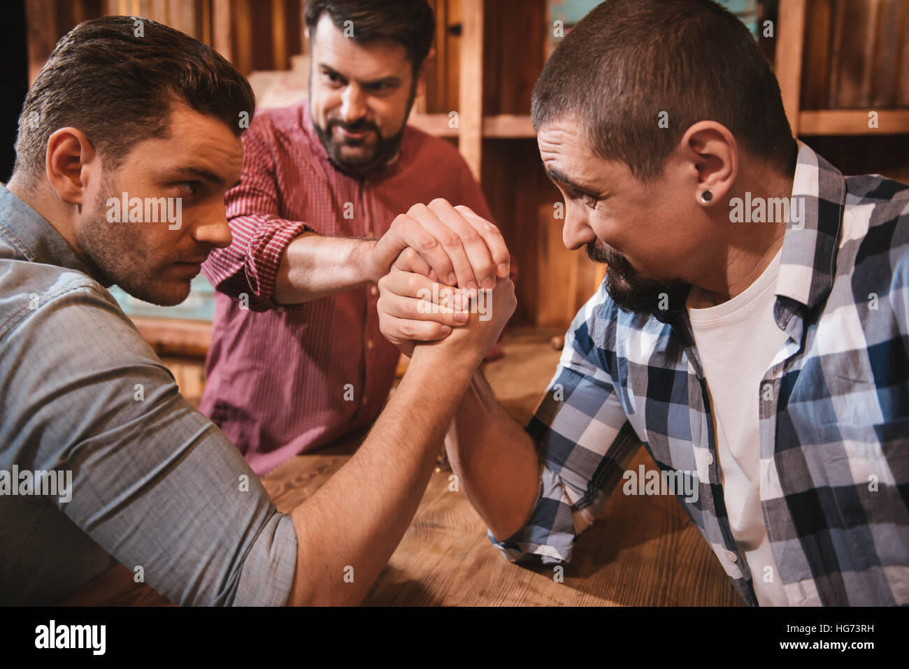 Handsome serious men preparing to start an armwrestling match - Stock Image