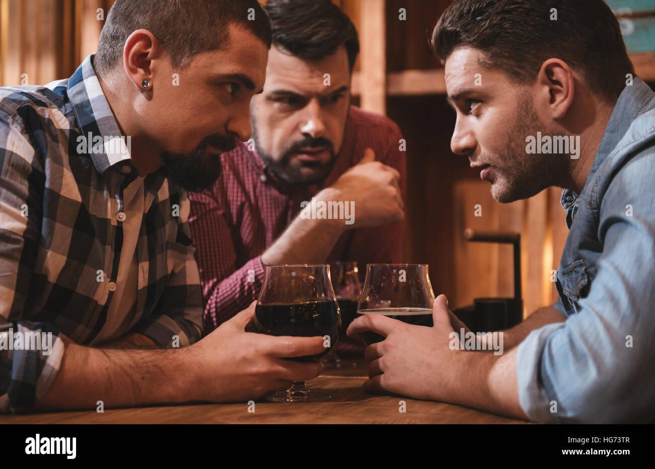 Handsome attractive men exchanging their secrets - Stock Image