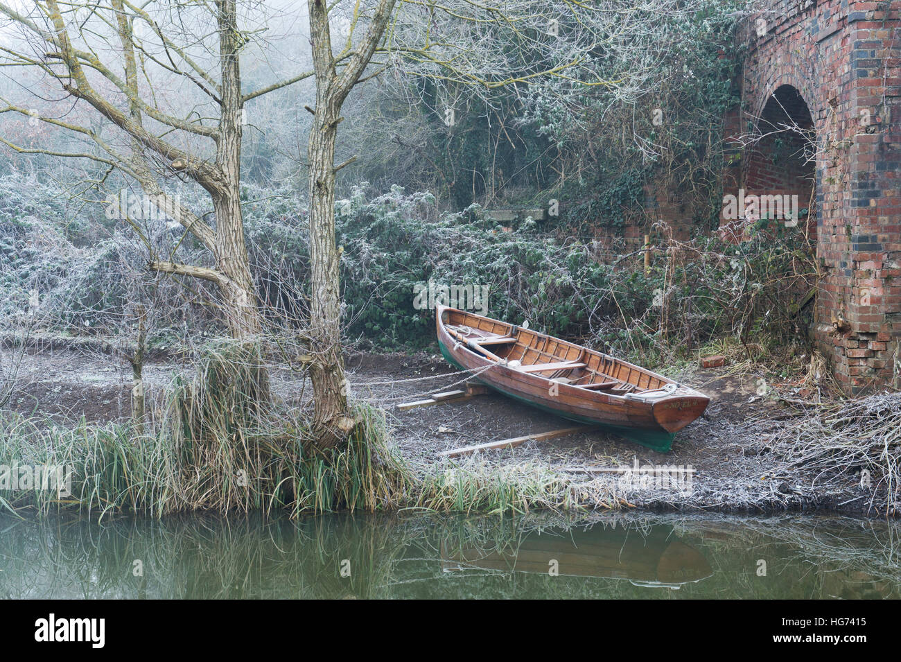 Wooden rowing boat by the Oxford canal on a frosty foggy December morning.  Oxfordshire, England - Stock Image