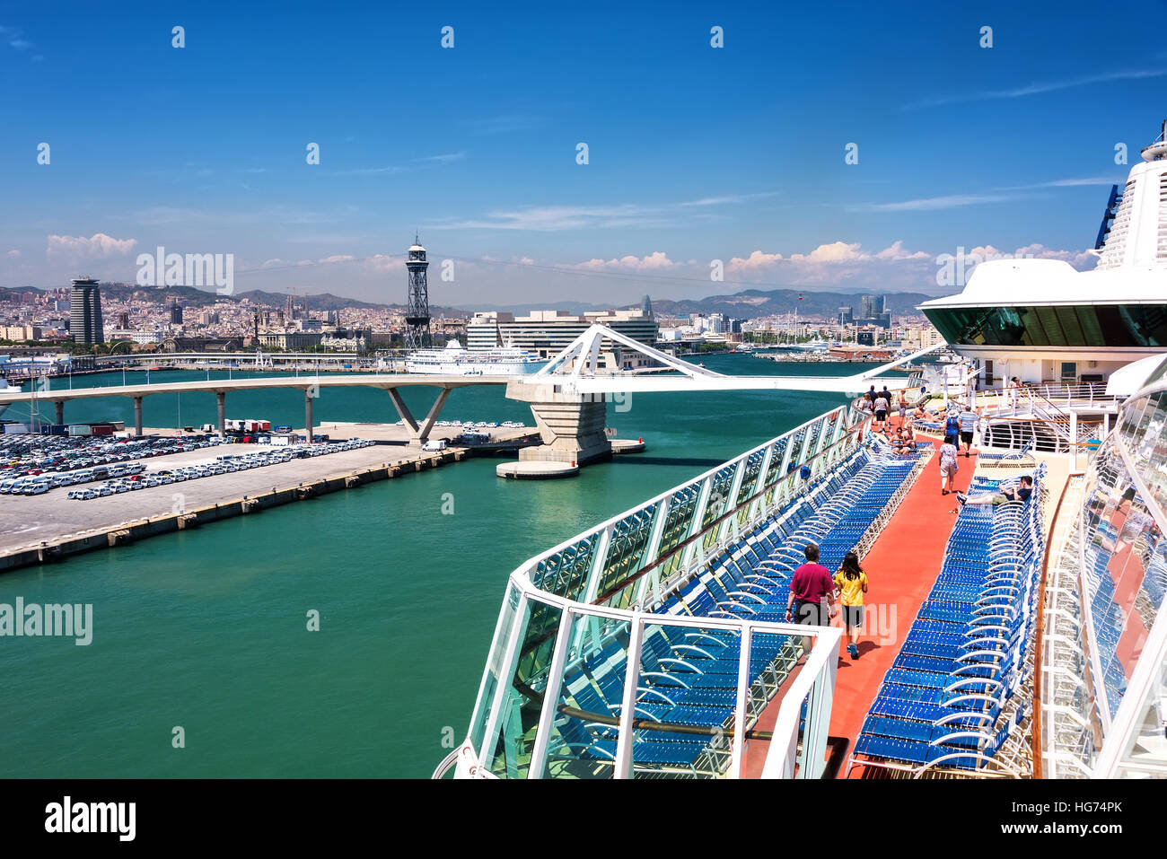 Cruise ship passengers stroll around the Lido Deck on a cruise ship anchored in port in Barcelona, Spain. - Stock Image