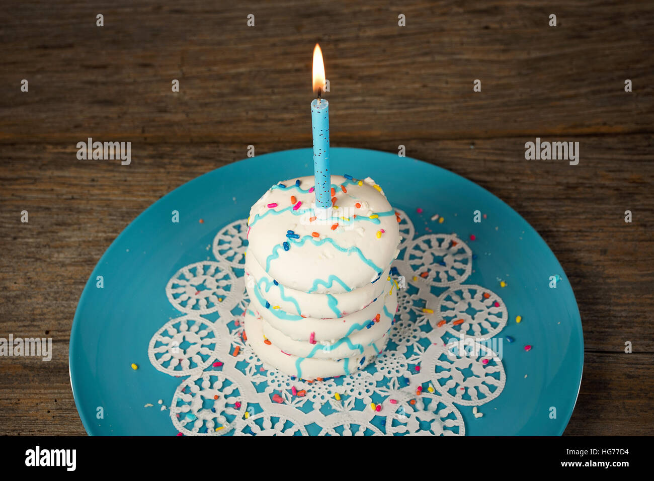Lit Birthday Candle On Stack Of Sugar Cookies With Sprinkles