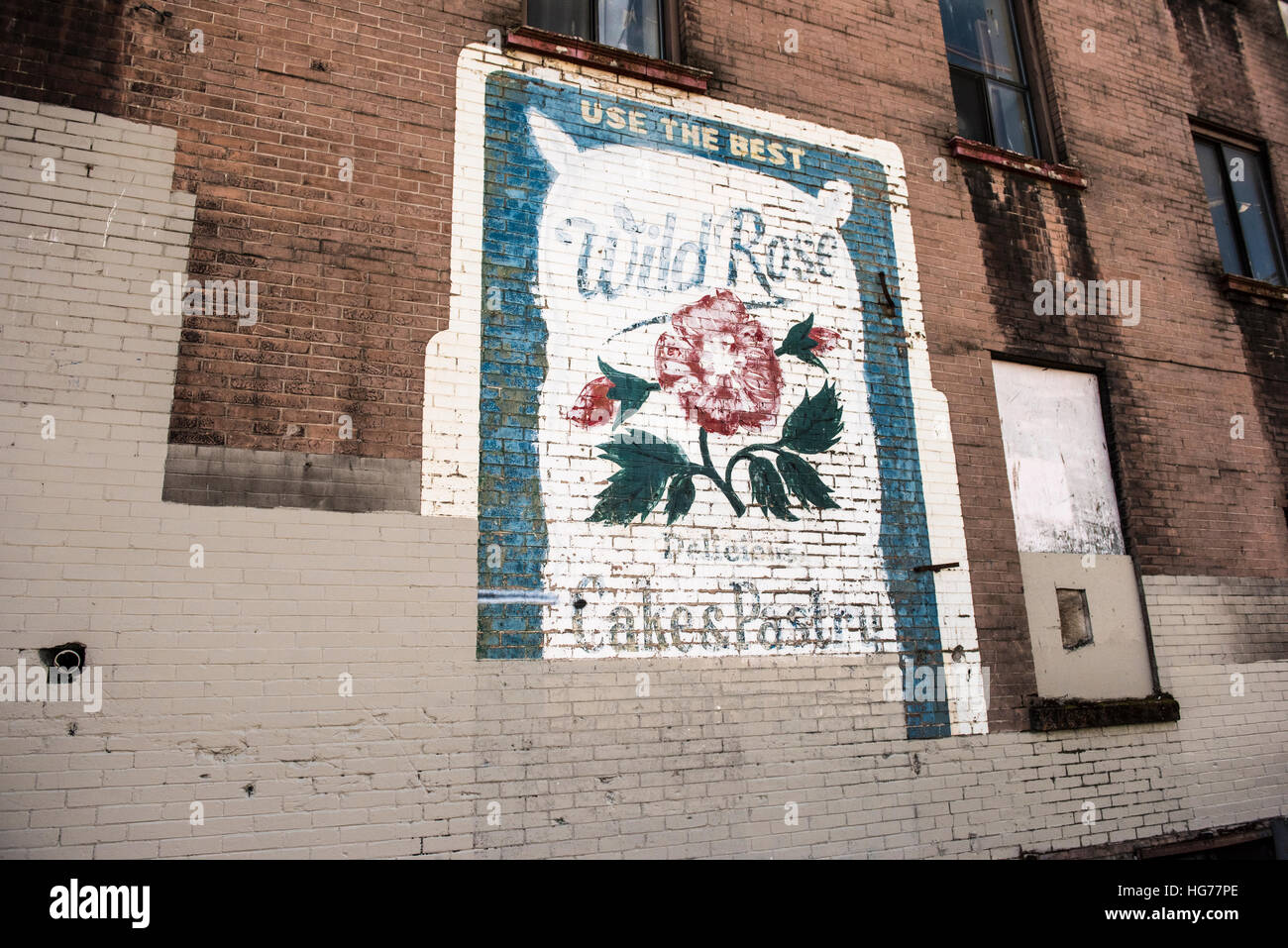 Old billboard ad painted on a brick building. - Stock Image