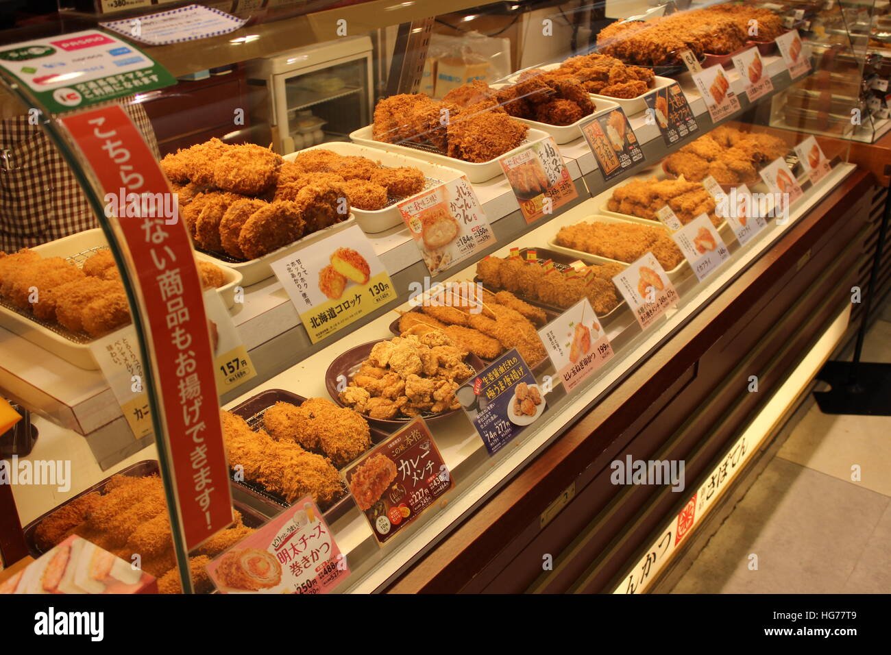 A case filled with various fried savory and sweet foods in Tokyo, Japan - Stock Image
