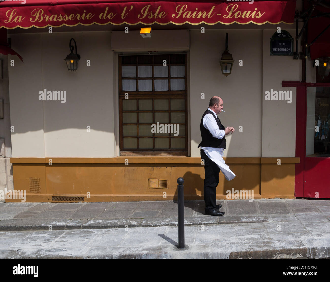 French waiter is lighting a cigarette in front of La Brasserie De L'Isle Saint Louis restaurant in Paris, France - Stock Image