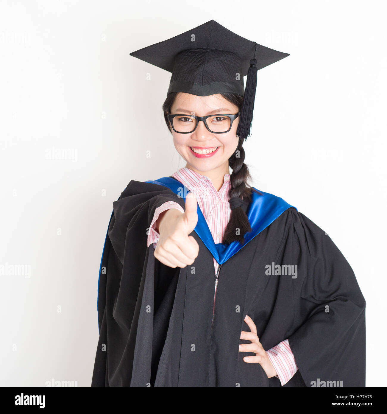 Happy university student in graduation gown and cap giving thumb up ...