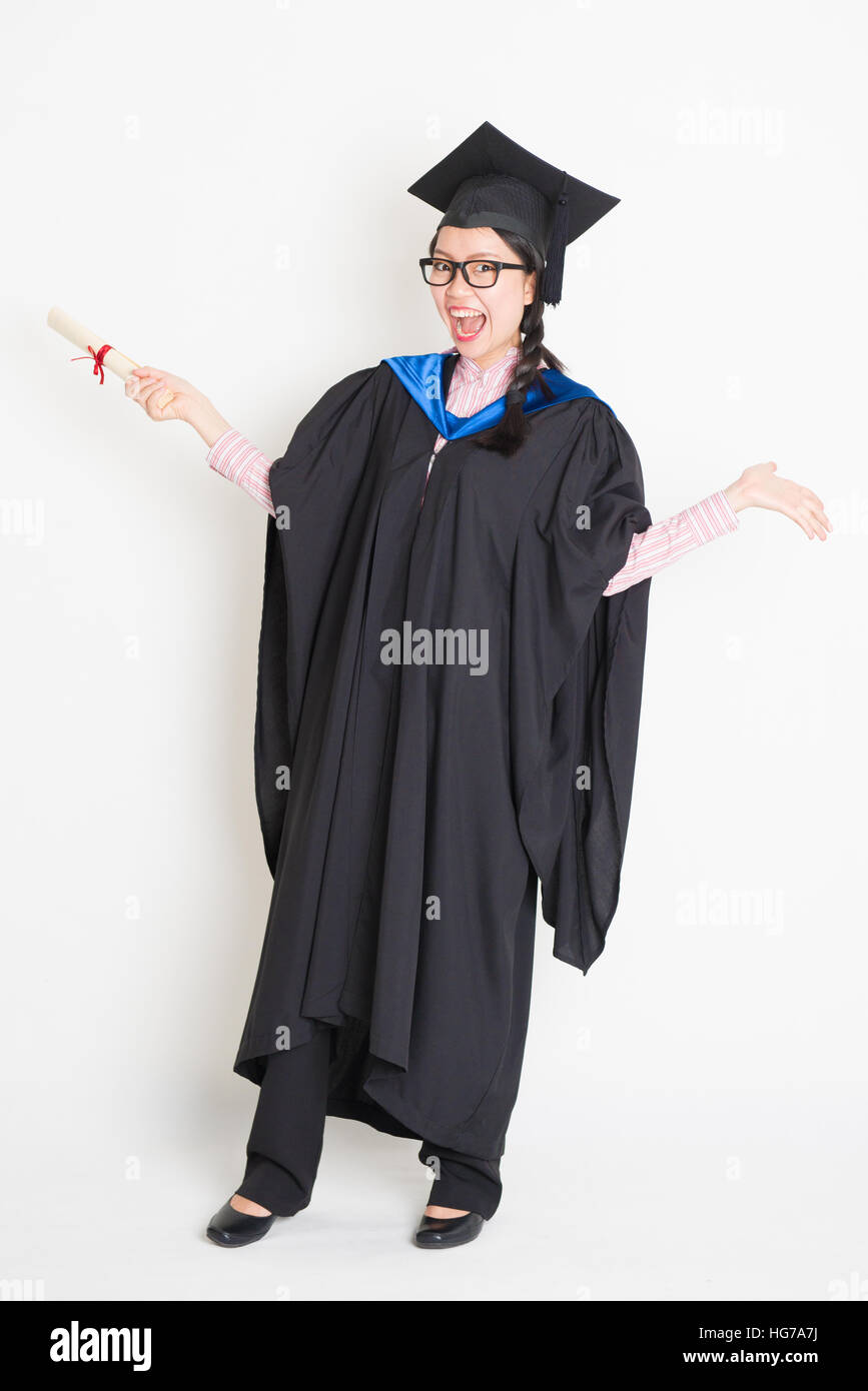 University student in graduation gown and cap holding diploma Stock ...