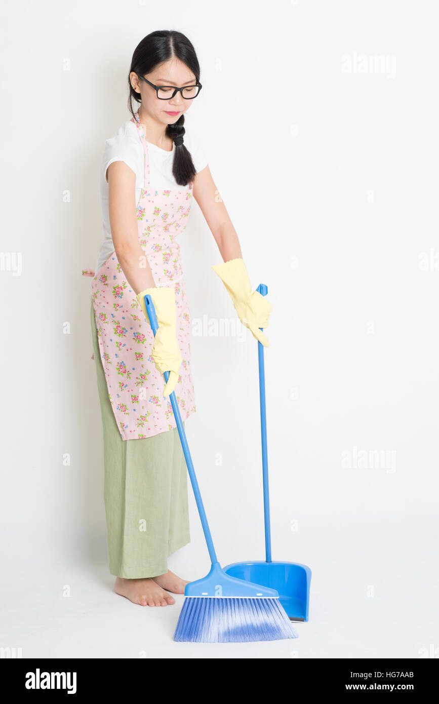 Young Asian Woman Sweeping Floor With Broom And Dustpan