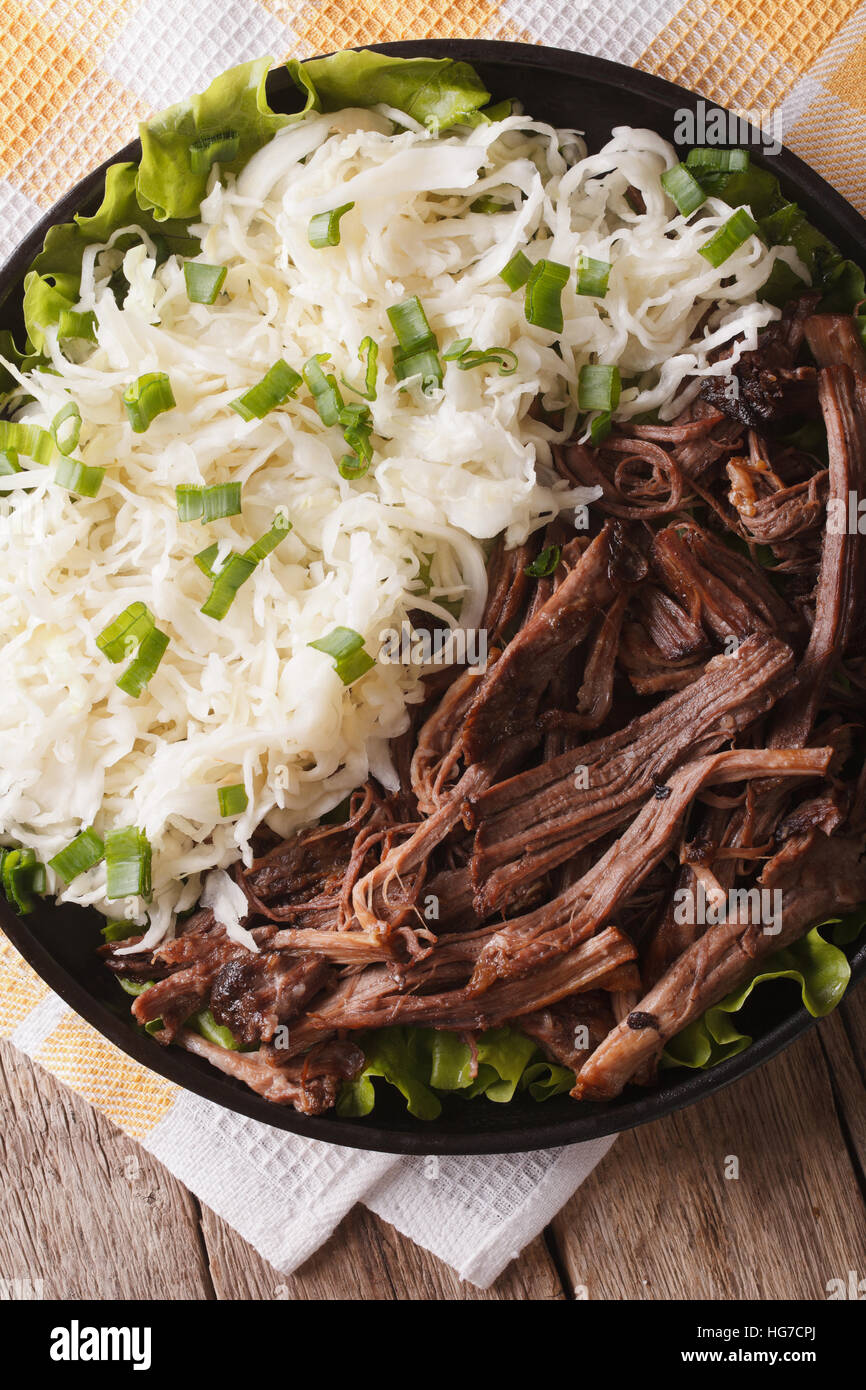Pulled pork with cabbage salad close-up on a plate. vertical top view - Stock Image
