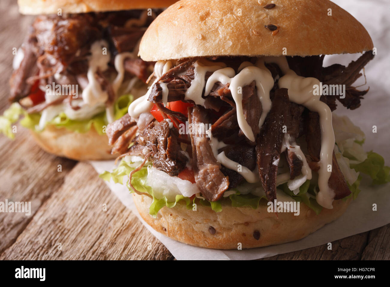 delicious Pulled pork sandwich with slaw and sauce close-up on the table. Horizontal - Stock Image