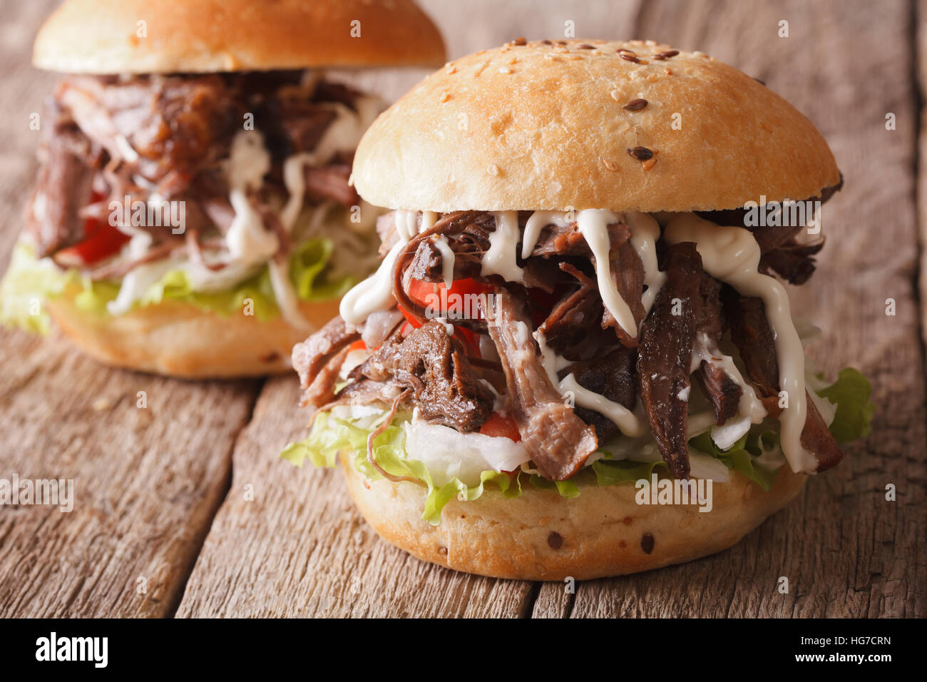 Pulled pork sandwich with vegetables and sauce close-up on the table. horizontal - Stock Image