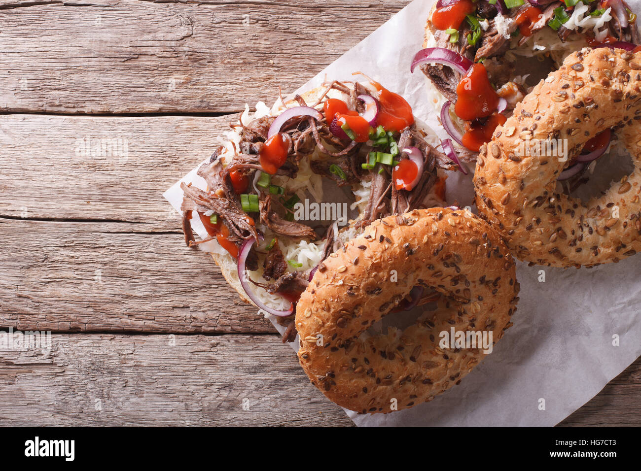 Bagels with Pulled pork, onions, cabbage and sauce on the table. horizontal view from above - Stock Image