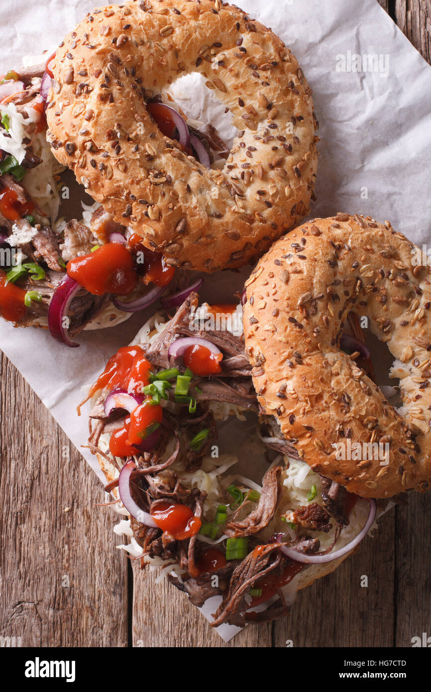 Bagels with Pulled pork, onions, cabbage and sauce close-up on the table. vertical top view - Stock Image