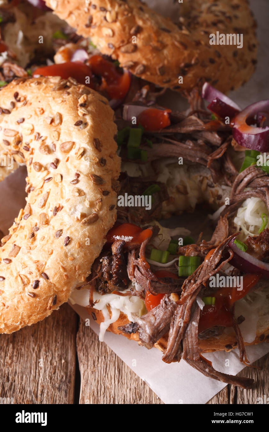 Bagel with vegetables and Pulled pork close-up on the table. vertical - Stock Image