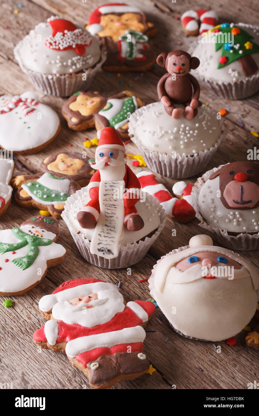 Delicious Christmas cupcakes and gingerbread close up on a wooden table. Vertical - Stock Image