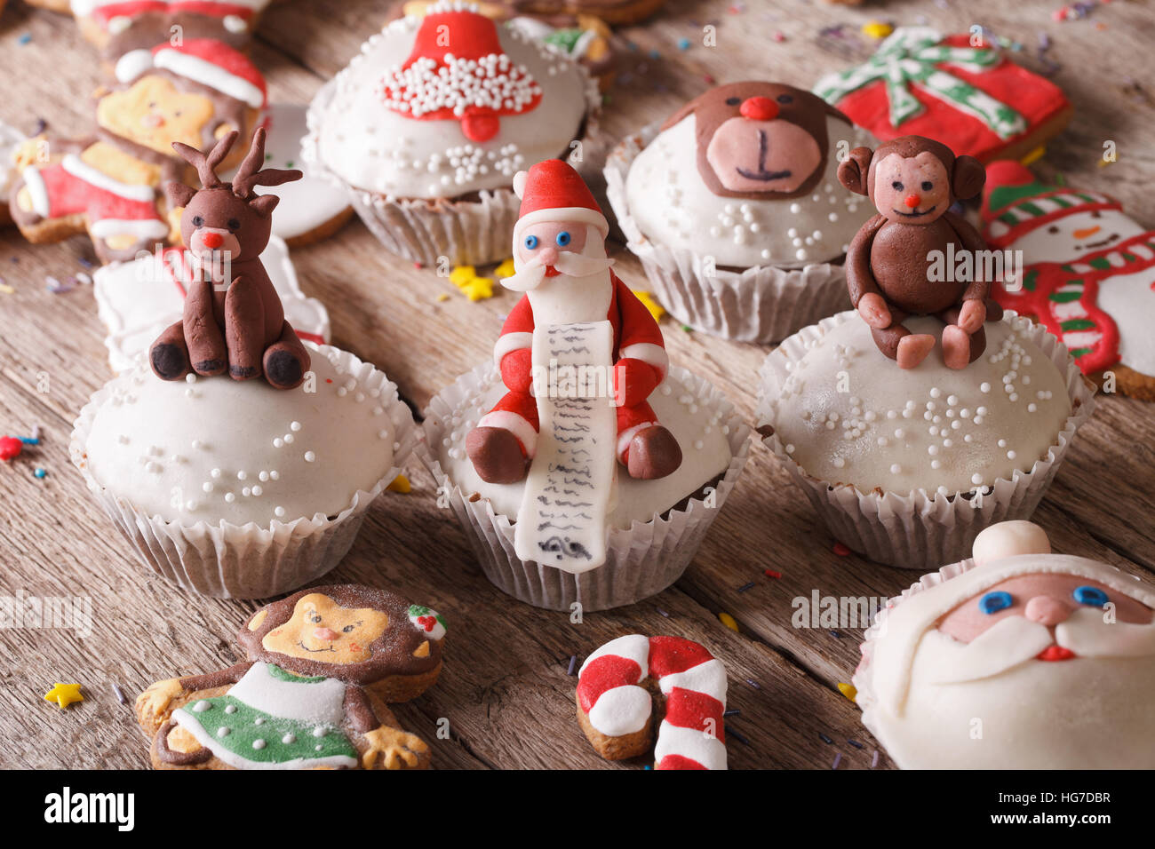 Beautiful Christmas sweets: cupcakes and gingerbread close up on a wooden table. Horizontal - Stock Image
