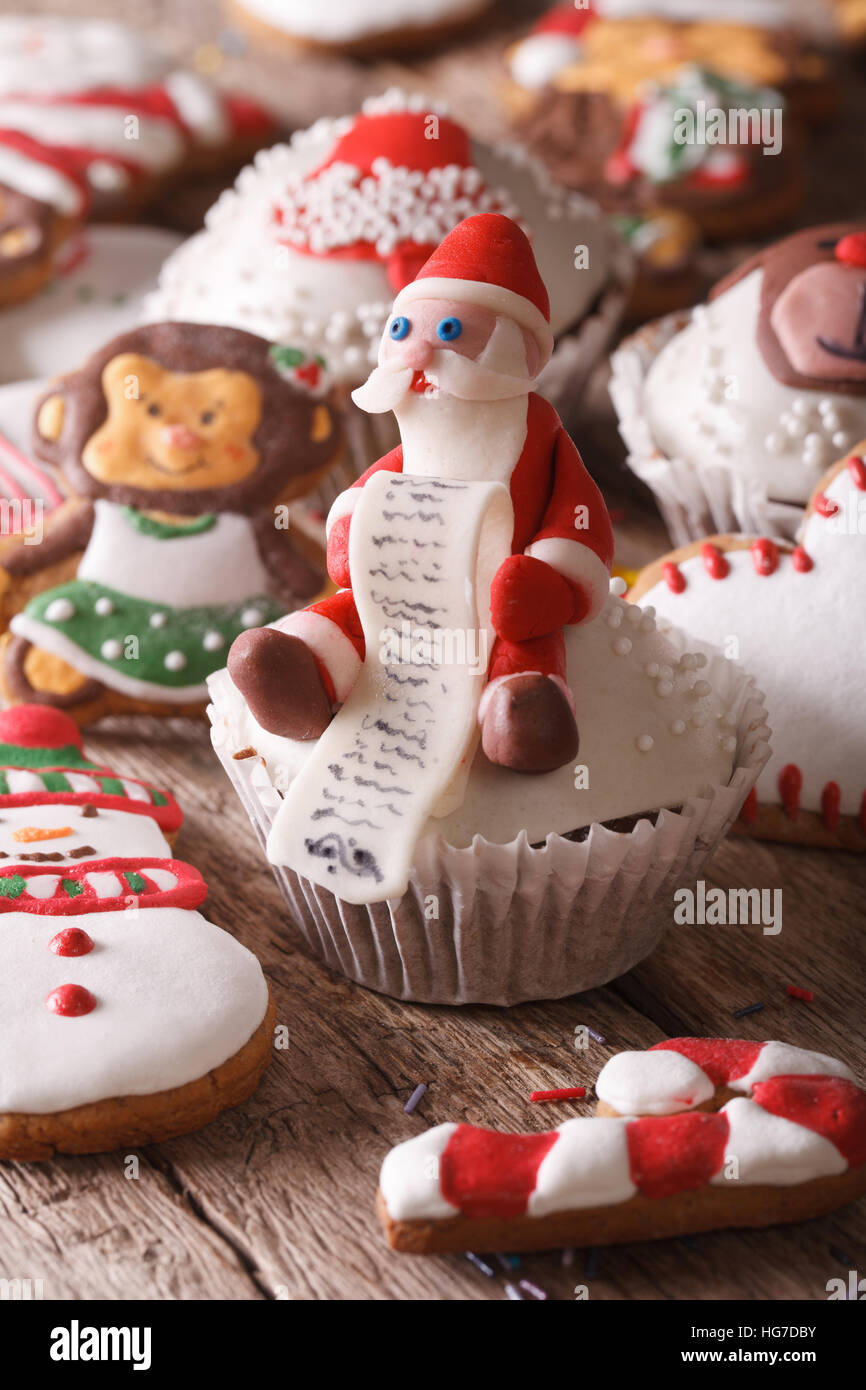 Christmas cupcakes and gingerbread cookies macro on a wooden table. Vertical - Stock Image