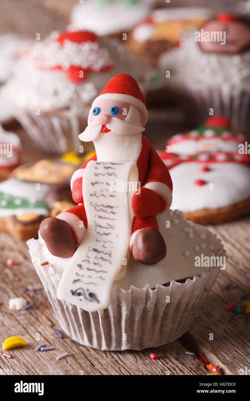Christmas cupcakes decorated with figures of Santa close-up on a wooden table. vertical - Stock Image
