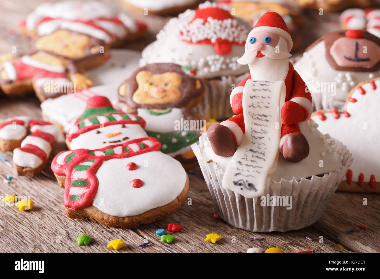 Christmas cupcakes and gingerbread cookies close-up on a wooden table. Horizontal - Stock Image